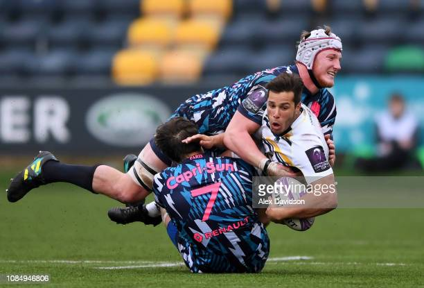 Dean Hammond of Worcester Warriors is tackled by Hendre Stassen of Stade Francais Paris and Sylvain Nicolas of Stade Francais Paris during the...