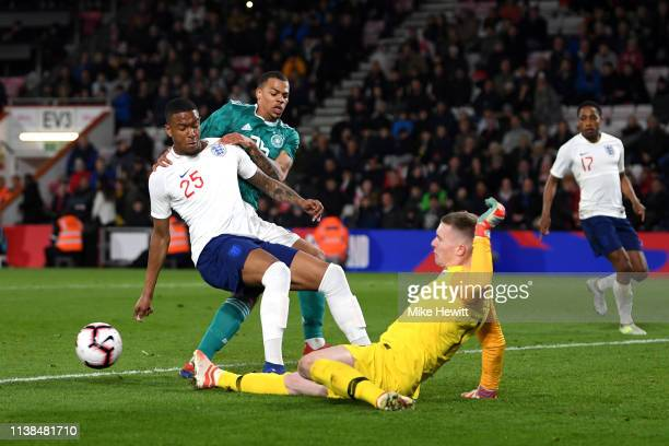 Dean Henderson of England makes a save from Lukas Nmecha of Germany as he is blocked by Ezri Konsa of England during the International Friendly match...