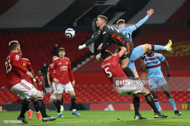 Dean Henderson of Manchester United punches the ball away as he collides with team mate Harry Maguire and Jarrod Bowen of West Ham United during the...
