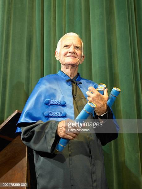 Dean holding diplomas