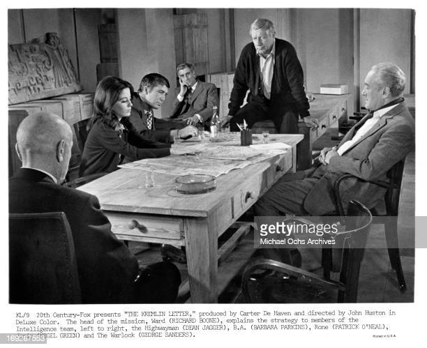 Dean Jagger Barbara Parkins Patrick O'Neal Nigel Green Richard Boone and George Sanders gathered around to discuss strategy in a scene from the film...