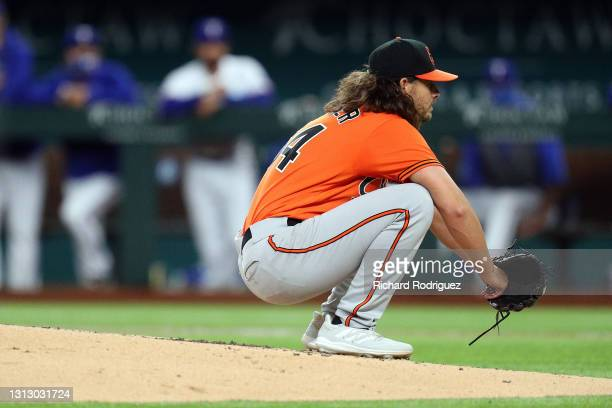Dean Kremer of the Baltimore Orioles crouches at the front of the mound in the fourth inning of the MLB game against the Texas Rangers at Globe Life...