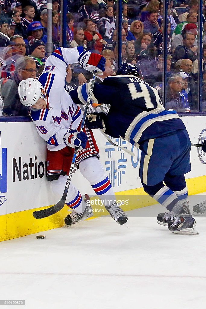 Dean Kukan #46 of the Columbus Blue Jackets checks Jesper Fast #19 of the New York Rangers into the boards while battling for control of a loose puck during the third period on April 4, 2016 at Nationwide Arena in Columbus, Ohio. New York defeated Columbus 4-2.