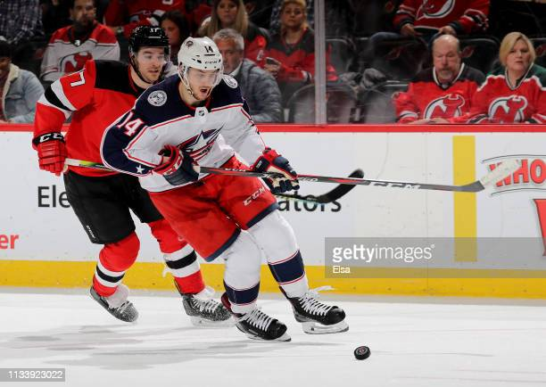 Dean Kukan of the Columbus Blue Jackets takes the puck as Kenny Agostino of the New Jersey Devils defends in the second period on March 05 2019 at...