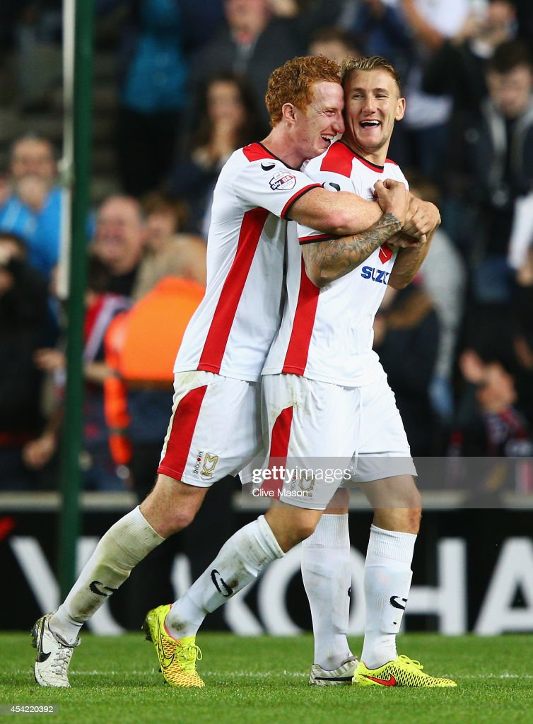 Dean Lewington (L) of Milton Keynes Dons celebrates his team's 4-0 victory with Kyle McFadzean after the Capital One Cup Second Round match between MK Dons and Manchester United at Stadium mk on August 26, 2014 in Milton Keynes, England.