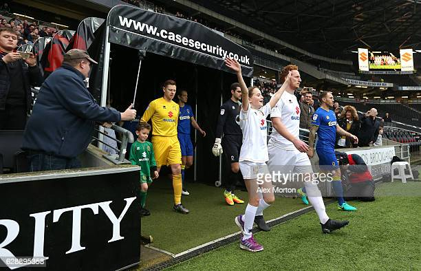Dean Lewington of MK Dons leads the MK Domerchandise for sale team out prior to kick off during the Sky Bet League One match between Milton Keynes...