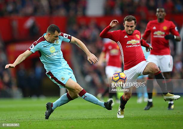Dean Marney of Burnley passes the ball while Juan Mata of Manchester United attempts to block during the Premier League match between Manchester...