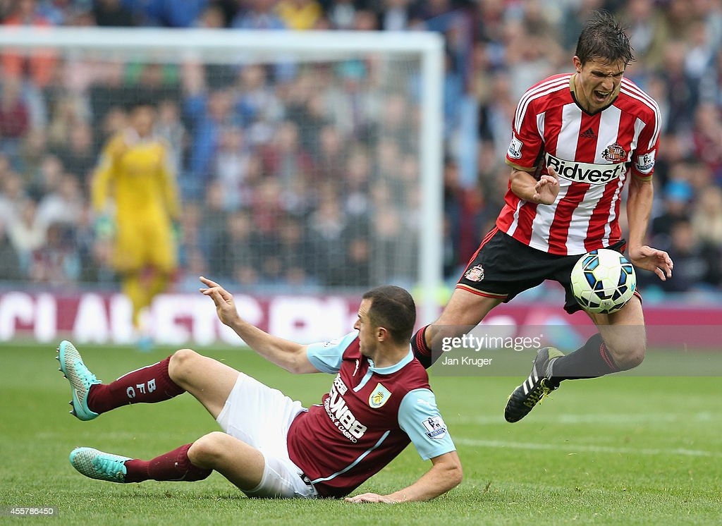 Dean Marney of Burnley tackles Santiago Vergini of Sunderland during the Barclays Premier League match between Burnley and Sunderland at Turf Moor on September 20, 2014 in Burnley, England.
