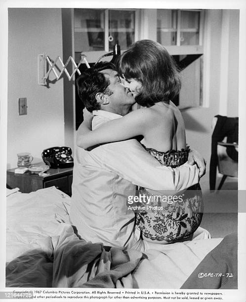 Dean Martin and Janice Rule sit on bed and embrace in a kiss in a scene from the film 'The Ambushers' 1967