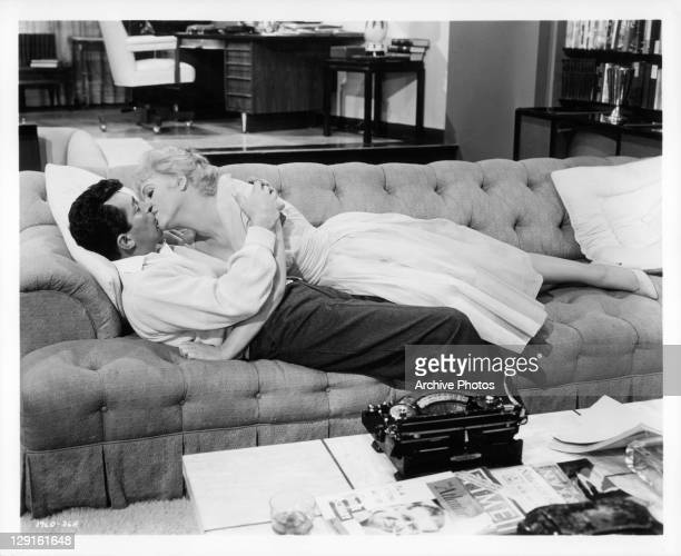 Dean Martin and Judy Holliday kissing on the couch in a scene from the film 'Bells Are Ringing' 1960