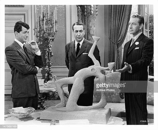 Dean Martin and Jules Munshin survey an unusual statue being presented to them by Paul Henreid in a scene from the film 'Ten Thousand Bedrooms' 1957