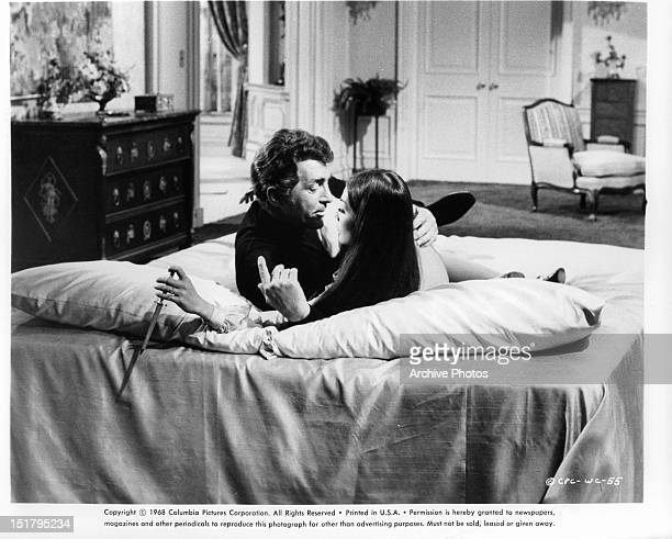 Dean Martin and Nancy Kwan recline in a bed together in a scene from the film 'The Wrecking Crew' 1968