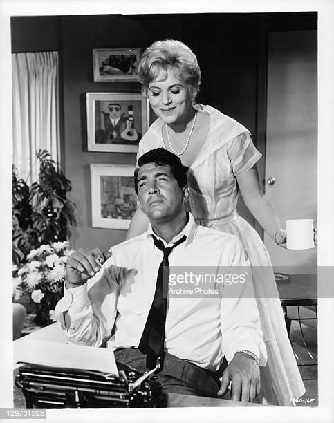Dean Martin enjoying a cigarette with Judy Holliday behind him in a scene from the film 'Bells Are Ringing' 1960