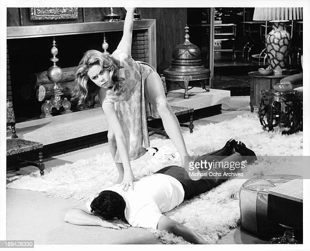 Dean Martin has his back stepped on by Elizabeth Montgomery in a scene from the film 'Who's Been Sleeping In My Bed' 1963