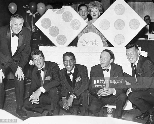 Dean Martin Sammy Davis Jr Danny Thomas Lucille Ball Frank Sinatra stand around a cake for the eleventh anniversary of the Sands Hotel in Las Vegas...