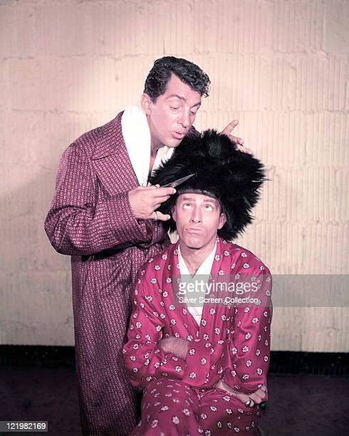 Dean Martin US actor and singer cutting a large black wig with a pair of scissors which is being worn by Jerry Lewis US actor and comedian borth are...