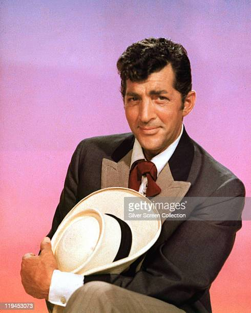 Dean Martin US actor and singer holding a cowboy hat and posing in costume for a studio portrait against a pink background 1960