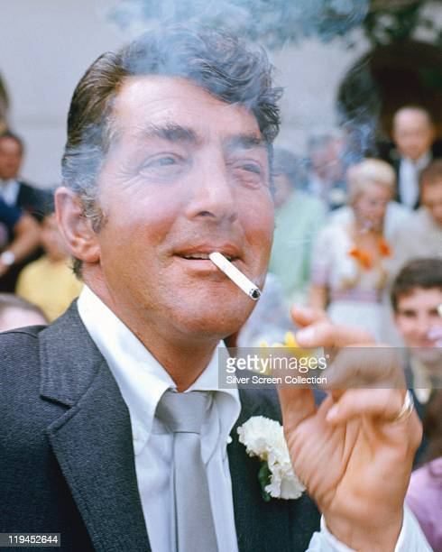 Dean Martin US actor and singer smoking a cigarette with a flower in the button hole of his jacket circa 1960