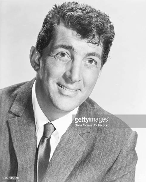 Dean Martin US actor and singer wearing a grey jacket over a white shirt with a dark tie in a studio portrait against a white background circa 1955