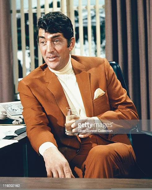 Dean Martin US singer and actor wearing a brown suit and holding a drink in a publicity portrait issued for the film 'The Silencers' USA 1967 The spy...