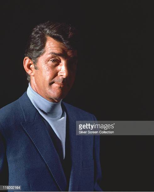 Dean Martin US singer and actor wearing a dark blue jacket and light blue polo neck jumper against a black background in a publicity portrait issued...