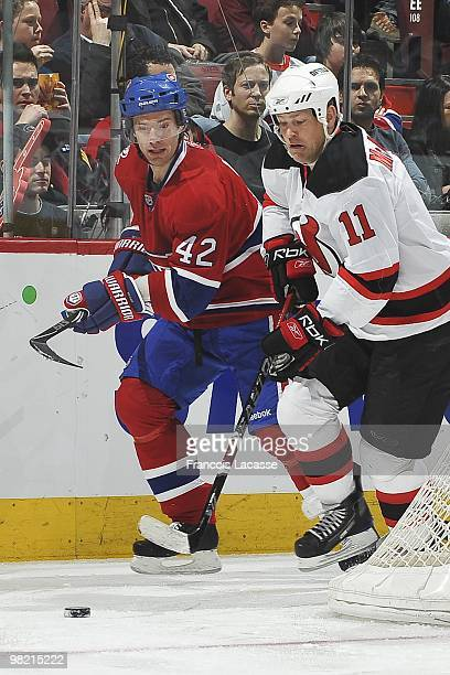 Dean McAmmond of New Jersey Devils skates wiht the puck in front of Dominic Moore of the Montreal Canadiens during the NHL game on March 27 2010 at...