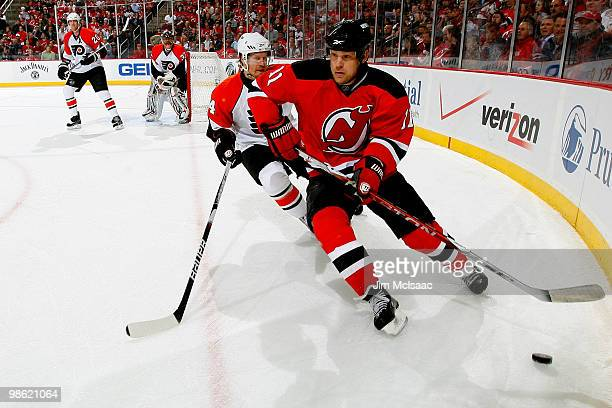 Dean McAmmond of the New Jersey Devils chases the puck along the boards against Kimmo Timonen of the Philadelphia Flyers in Game 5 of the Eastern...