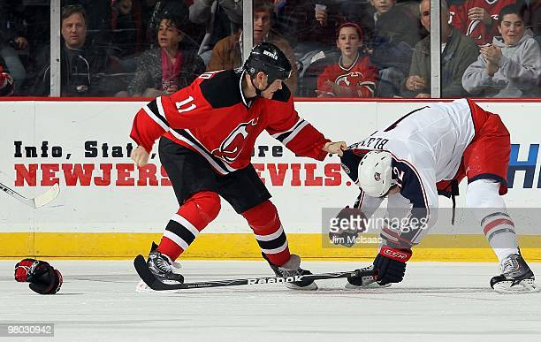 Dean McAmmond of the New Jersey Devils throws a punch at Mike Blunden of the Columbus Blue Jackets at the Prudential Center on March 23 2010 in...