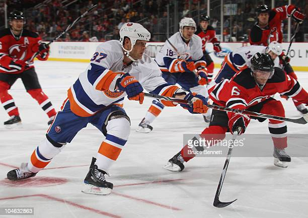 Dean McAmmond of the New York Islanders backhands the puck past Andy Greene of the New Jersey Devils at the Prudential Center on October 1 2010 in...