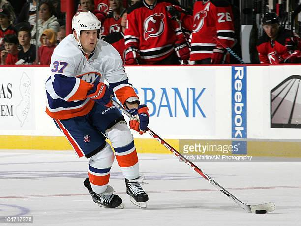 Dean McAmmond of the New York Islanders plays the puck against the New Jersey Devils during the preseason game at the Prudential Center on October 1...
