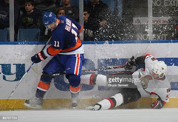 Dean McAmmond of the Ottawa Senators is hit by Andy Hilbert of the New York Islanders on November 15 2008 at the Nassau Coliseum in Uniondale New York