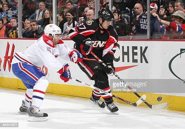 Dean McAmmond of the Ottawa Senators stick handles the puck against Francis Bouillon the Montreal Canadiens at Scotiabank Place on January 17 2009 in...