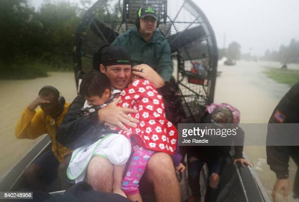 Dean Mize holds children as he and Jason Legnon use an airboat to rescue people from homes that are inundated with flooding from Hurricane Harvey on...