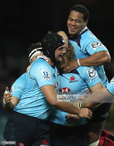 Dean Mumm and John Ulugia of the Waratahs congratulate Ryan Cross of the Waratahs after he scored a try during the round 12 Super Rugby match between...