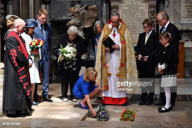 Dean of Westminster John Hall accompanied by first wife Jane Hawking watches as daughter Lucy Hawking places flowers at the site of the internment of...