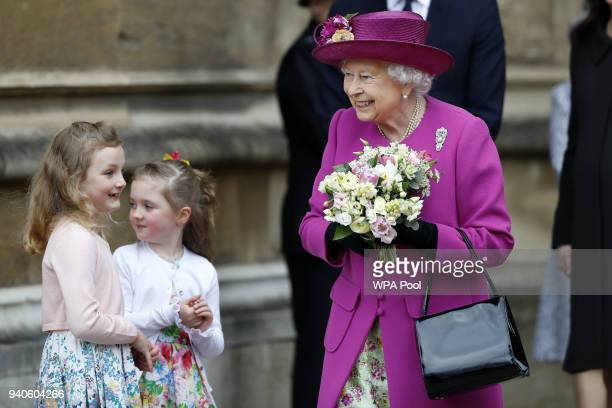 Dean of Windsor David Conner looks on as Queen Elizabeth II is greets with flowers from children after the Easter Mattins Service at St George's...