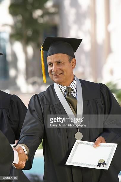 Dean presenting diploma at graduation ceremony