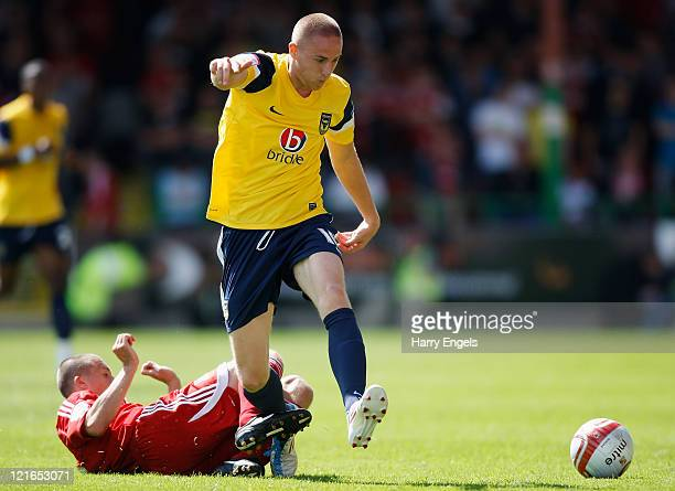 Dean Smalley of Oxford United is tackled by Paul Caddis of Swindon Town during the npower League Two match between Swindon Town FC and Oxford United...