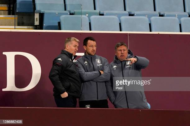 Dean Smith, Manager of Aston Villa and Assistant Managers John Terry and Craig Shakespeare discuss during the Premier League match between Aston...