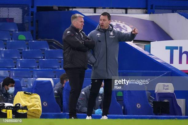 Dean Smith, manager of Aston Villa speaks with assistant manager John Terry during the Premier League match between Chelsea and Aston Villa at...