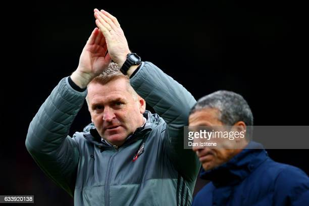 Dean Smith manager of Brentford applauds the fans as he walks out with Chris Hughton manager of Brighton Hove Albion during the Sky Bet Championship...