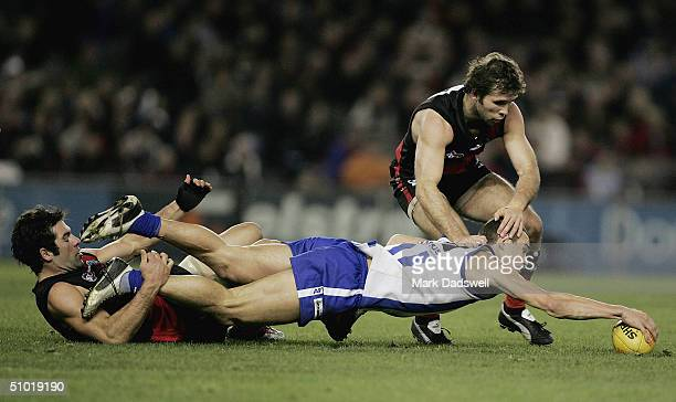 Dean Solomon and Mark McVeigh for the Bombers tackle Corey Jones for the Kangaroos during the round 14 AFL match between the Essendon Bombers and the...