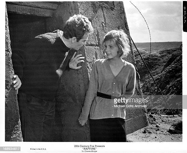 Dean Stockwell and Patricia Gozzi next to a cement building in a desolate area in a scene from the film 'Rapture' 1965