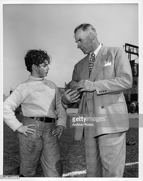 Dean Stockwell gets a few football pointers from Coach Bill Spaulding former mentor of the UCLA Bruins in a scene from the film 'The Happy Years' 1950