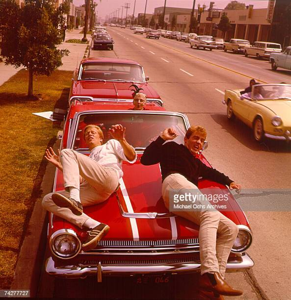 Dean Torrence and Jan Berry and Kathryn Minner pose and for a portrait on the hood of 'a brand new shiny red super stocked Dodge in 1964 in Los...