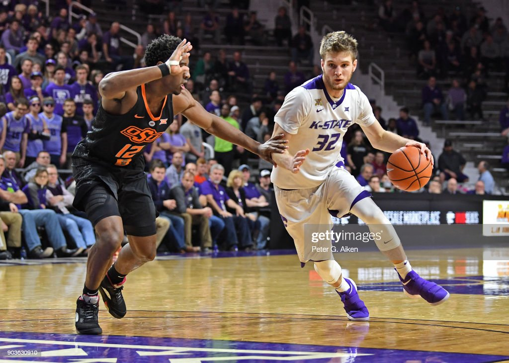 Dean Wade #32 of the Kansas State Wildcats drives with the ball against Cameron McGriff #12 of the Oklahoma State Cowboys during the second half on January 10, 2018 at Bramlage Coliseum in Manhattan, Kansas.