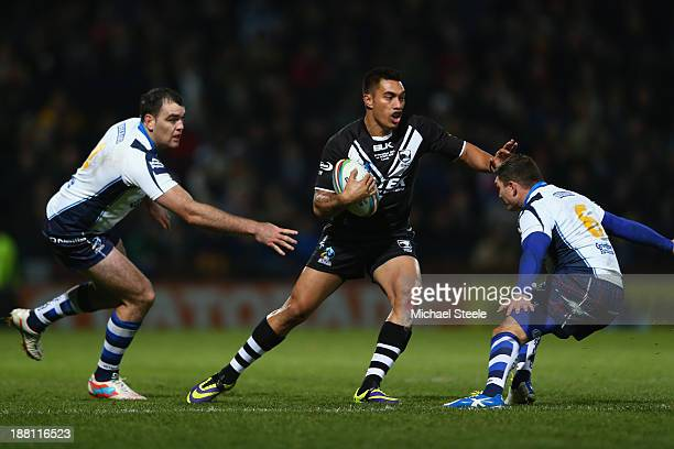 Dean Whare of New Zealand sidesteps Kane Linnett and Danny Brough of Scotland during the Rugby League World Cup Quarter Final match between New...