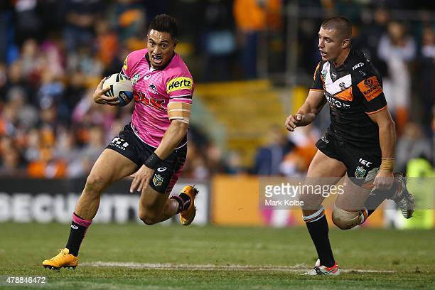 Dean Whare of the Panthers evades Kyle Lovett of the Wests Tigers during the round 16 NRL match between the Wests Tigers and the Penrith Panthers at...