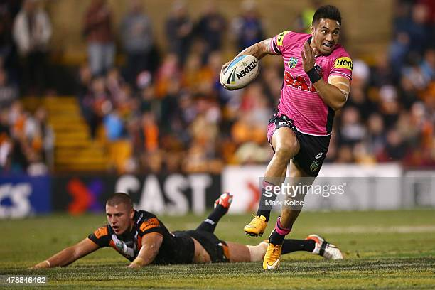 Dean Whare of the Panthers evades the tackle of Kyle Lovett of the Wests Tigers during the round 16 NRL match between the Wests Tigers and the...