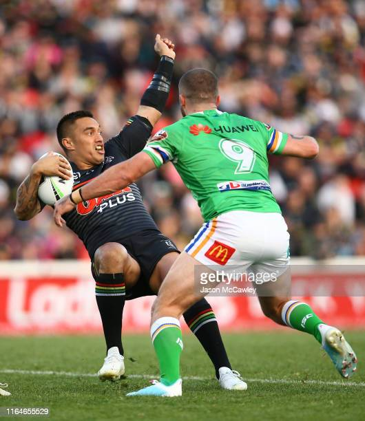 Dean Whare of the Panthers is tackled by Josh Hodgson of the Raiders during the round 19 NRL match between the Panthers and Raiders at Panthers...